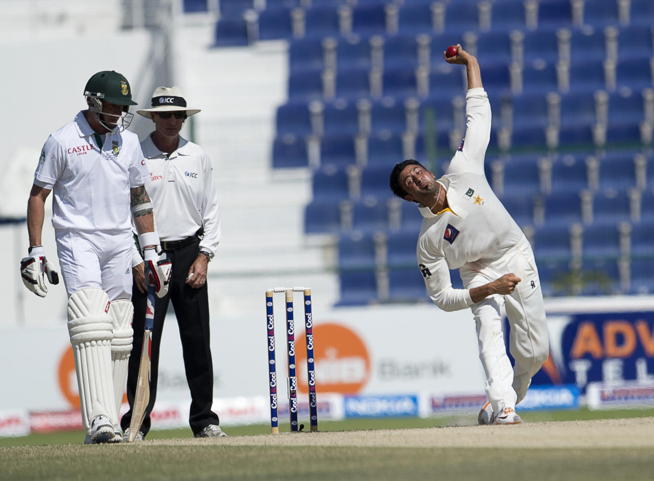 Pakistan Junaid Khan bows as South Africa's batsman Dale Styn stands on the fourth day of their first Test against South Africa at the Sheikh Zayed Cricket Stadium in Abu Dhabi on October 17, 2013. AB de Villiers hit a fighting fifty to delay Pakistan's victory march over South Africa on the fourth day of the first Test in Abu Dhabi today. AFP PHOTO/STR        (Photo credit should read STR/AFP/Getty Images)