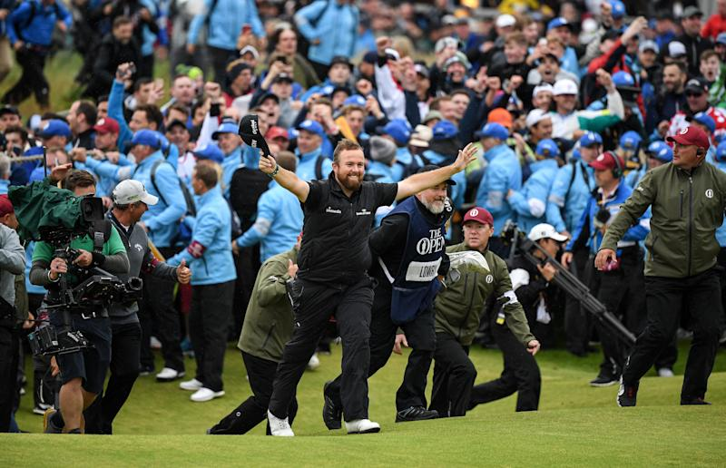 Shane Lowry of Ireland walks up the 18th fairway, arms aloft taking the crowds applause on his way to securing victory during the final round of the 148th Open Championship at Royal Portrush