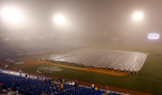 Grounds crew members cover the field after play was suspended due to fog during the sixth inning of a Southeastern Conference tournament NCAA college baseball game between Florida and LSU, late Friday, May 25, 2018, in Hoover, Ala. The game is scheduled to resume late Saturday morning. (AP Photo/Butch Dill)