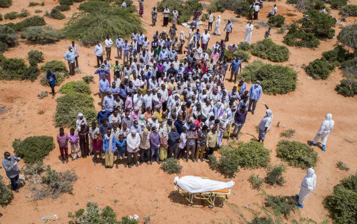 FILE - In this April 30, 2020, file photo, mourners gather to bury an elderly man believed to have died of the coronavirus in Mogadishu, Somalia. Africa has surpassed 100,000 confirmed deaths from COVID-19 as the continent praised for its early response to the pandemic now struggles with a dangerous resurgence and medical oxygen often runs desperately short. (AP Photo, File)