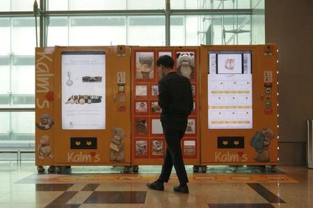 A traveller browses gifts at a vending machine by premium gift brand Kalms at Singapore's Changi Airport Terminal 3, Singapore March 6, 2018. Picture taken March 6, 2018. REUTERS/Dewey Sim