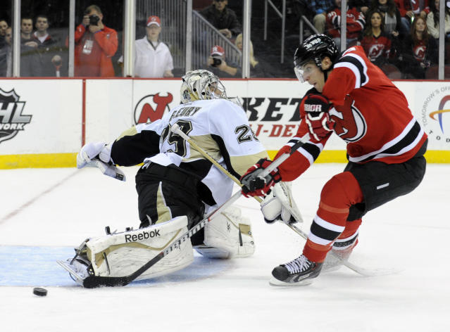 Pittsburgh Penguins goaltender Marc-Andre Fleury, left, forces New Jersey Devils' Steve Bernier to shoot the puck wide of the net as he comes in on a breakaway during the second period of an NHL hockey game Saturday, Nov. 16, 2013, in Newark, N.J. (AP Photo/Bill Kostroun)