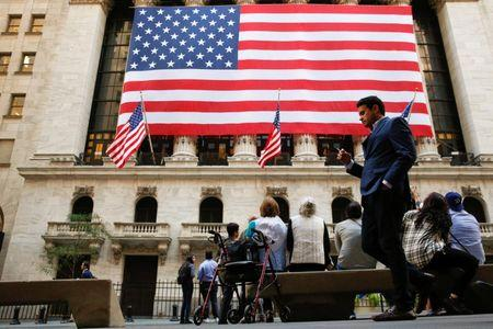 People sit outside the NYSE