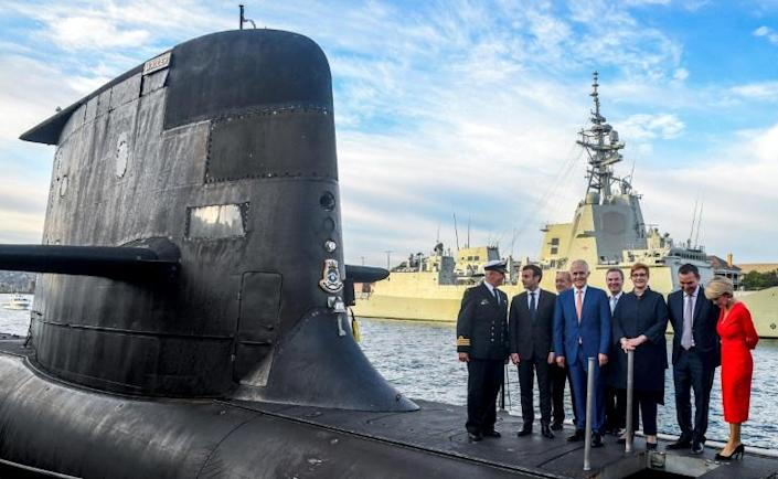 French President Emmanuel Macron tours the deck of a submarine with Australia's then prime minister Malcolm Turnbull in Sydney in May 2018 (AFP/BRENDAN ESPOSITO)