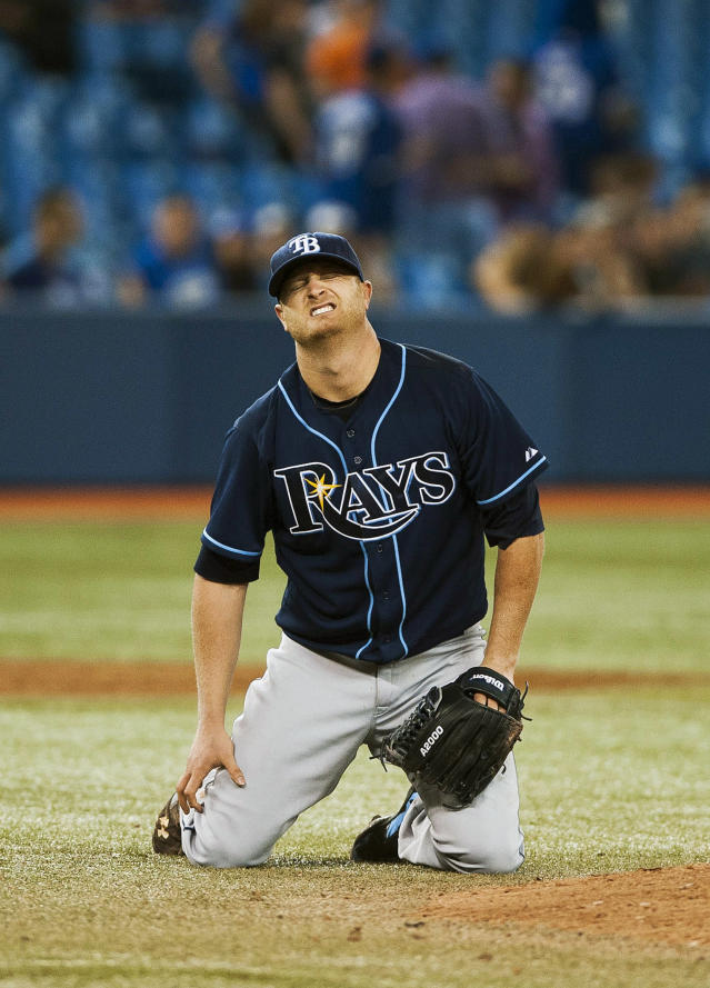 Tampa Bay Rays' Alex Cobb reacts after getting hit by a ball from Toronto Blue Jays' Jose Reyes during the fifth inning of a baseball game in Toronto on Tuesday, May 27, 2014. (AP Photo/The Canadian Press, Aaron Vincent Elkaim)
