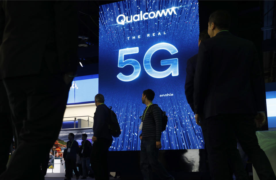 FILE- In this Jan. 9, 2019, file photo a sign advertises 5G at the Qualcomm booth at CES International in Las Vegas. Qualcomm and Apple drove declines in technology stocks on Wednesday, May 22. Qualcomm plunged following a federal judge's ruling against the chipmaker in an antitrust case. (AP Photo/John Locher, File)