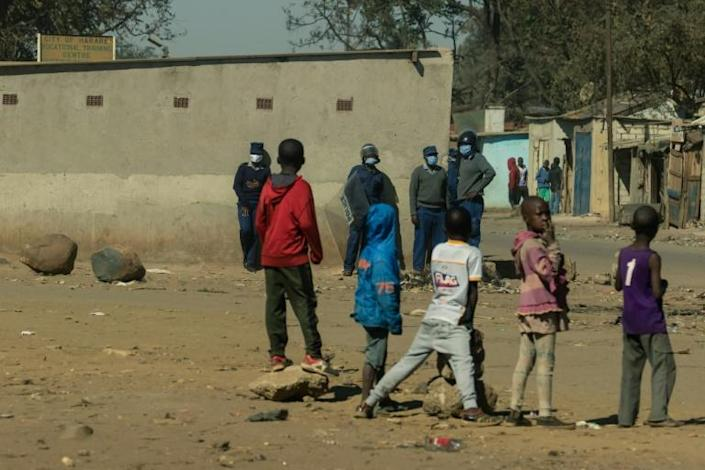 A group of children look on as a team of police are deployed in Mbare township following a ban on anti-government protests last month