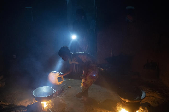 Lighted by a flashlight, a girl stokes the fire as the food is prepared in a compound at the Sare Gibel village in Bansang, Gambia, Wednesday, Sept. 29, 2021. As health officials in Gambia and across Africa urge women to be vaccinated, they've confronted hesitancy among those of childbearing age. Although data on gender breakdown of vaccine distribution are lacking globally, experts see a growing number of women in Africa's poorest countries consistently missing out on vaccines. (AP Photo/Leo Correa)