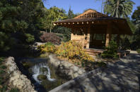 A Japanese-style open-air Pavilion, used for reflection, mindfulness and community classes stands next to a Japanese wisteria and a waterfall in the Japanese Garden at Lotusland, Monday, Nov. 23, 2020, in Montecito, Calif. The sounds of rushing water are heard while walking on the footpaths nearby before seeing the source.(AP Photo/Pamela Hassell)