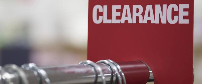 RED CLEARANCE SIGN ON CLOTH RACK (The Image Has Shallow Depth Of Field)