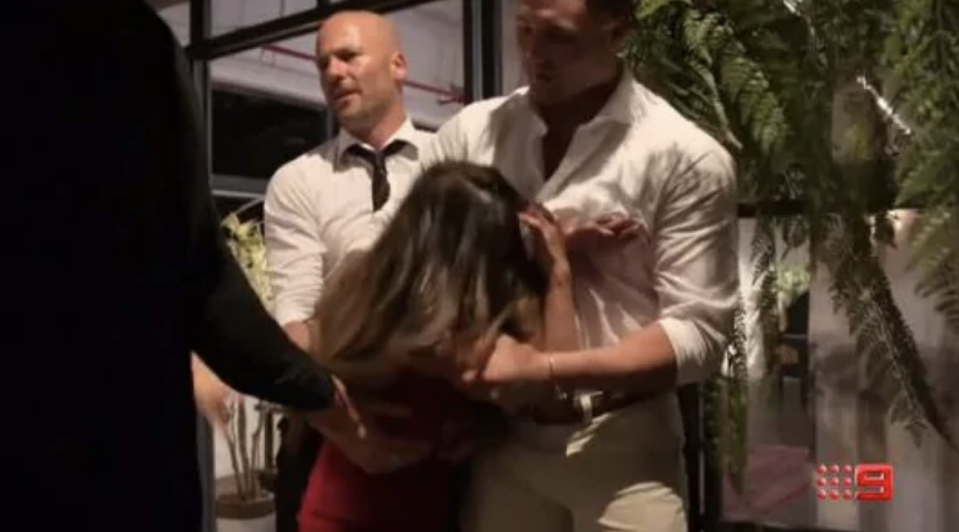 Cyrell Paule is held back by Mike Gunner and other male contestants during a heated argument on Married At First Sight 2019