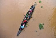 FILE PHOTO: Flood-affected villagers are transported by boat to safety at Kachua village