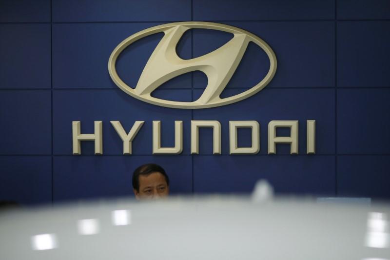 An employee sits in front of the logo of Hyundai Motor Co. at its dealership in Seoul