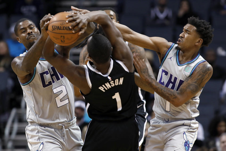 Charlotte Hornets' Marvin Williams (2) teams up with Malik Monk (1) to steal the ball away from Brooklyn Nets' Theo Pinson (1) during the second half of an NBA basketball game in Charlotte, N.C., Friday, Dec. 6, 2019. The Nets won 111-104. (AP Photo/Bob Leverone)