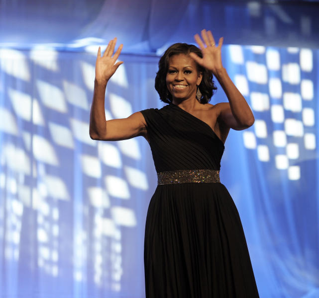 First lady Michelle Obama waves as she is introduced onstage to address the Congressional Black Caucus Foundation's 42nd Annual Phoenix Awards dinner in Washington, Saturday, Sept. 22, 2012. (AP Photo/Cliff Owen)