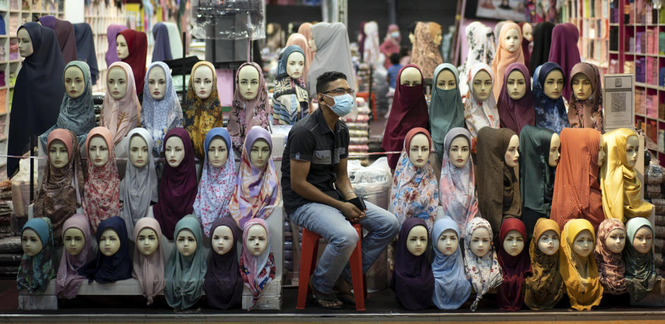 A shop vendor wearing a face mask to help curb the spread of the coronavirus waits for customers in downtown Kuala Lumpur, Malaysia, on Tuesday, Nov. 3, 2020. Malaysia extended restricted movements in its biggest city Kuala Lumpur, neighboring Selangor state and the administrative capital of Putrajaya from Wednesday in an attempt to curb a sharp rise in coronavirus cases. (AP Photo/Vincent Thian)