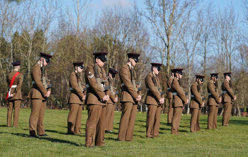 BEDFORD, ENGLAND - FEBRUARY 27: (EDITOR'S NOTE: No reuse after 11.59pm on March 6th 2021 without written consent from gemma@captaintom.org.) Members of the Armed Forces stand in formation during a private funeral service for Captain Sir Tom Moore at Bedford Crematorium on February 27, 2021 in Bedford, England. WWII veteran, Sir Tom raised nearly £33 million for NHS charities ahead of his 100th birthday last year by walking laps of his garden in Marston Moretaine, Bedfordshire. He died on the 2nd of February after testing positive for COVID-19. (Photo by Joe Giddens - Pool/Getty Images)