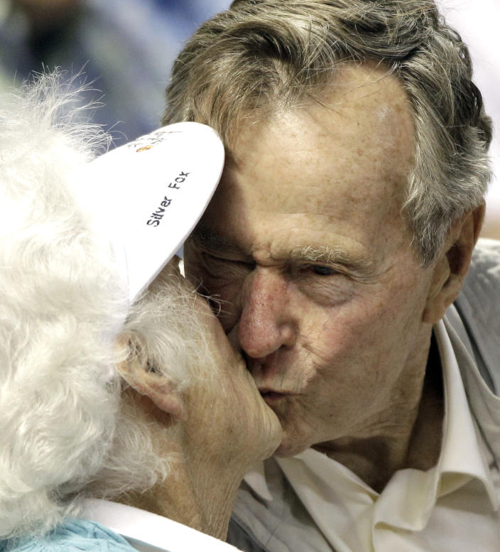 <p>Former President George H.W. Bush kisses his wife, Barbara, after both were shown on the stadium kiss cam video board during a baseball game between the Houston Astros and the Arizona Diamondbacks on May 5, 2010, in Houston. (Photo: David J. Phillip/AP) </p>