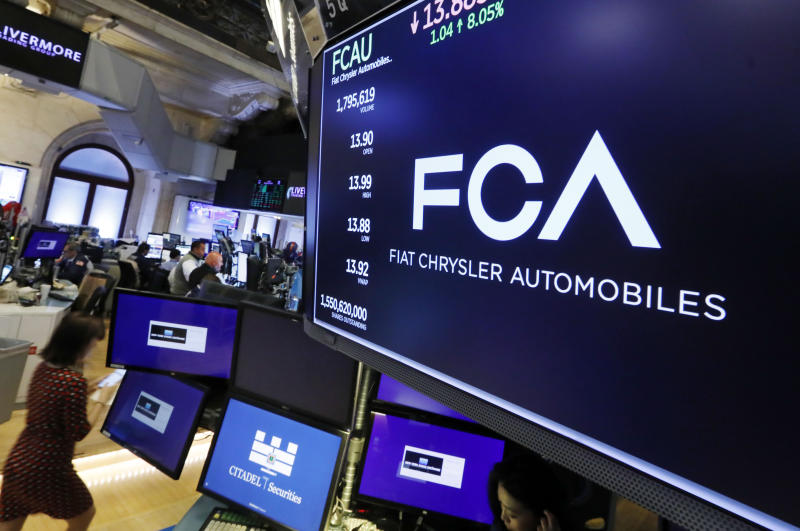 FILE - In this May 28, 2019, file photo, the Fiat Chrysler Automobiles logo appears above a post on the floor of the New York Stock Exchange. Japanese automaker Nissan wasn't consulted about a proposed merger between its French alliance partner Renault and Fiat Chrysler and has little say over the issue. Partnering with a colossal Renault-Fiat Chrysler could help Nissan slash costs on shared components and research. (AP Photo/Richard Drew, File)