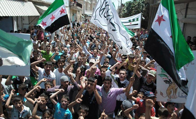 """This citizen journalism image provided by Shaam News Network SNN, taken on Friday, July 6, 2012, purports to show protesters waving Syrian revolutionary flags and chanting slogans during a demonstration in Idlib, north Syria. Syria's military began large-scale exercises simulating defense against outside """"aggression,"""" the state-run news agency said Sunday an apparent warning to other countries not to intervene in the country's crisis. (AP Photo/Shaam News Network, SNN)THE ASSOCIATED PRESS IS UNABLE TO INDEPENDENTLY VERIFY THE AUTHENTICITY, CONTENT, LOCATION OR DATE OF THIS HANDOUT PHOTO"""