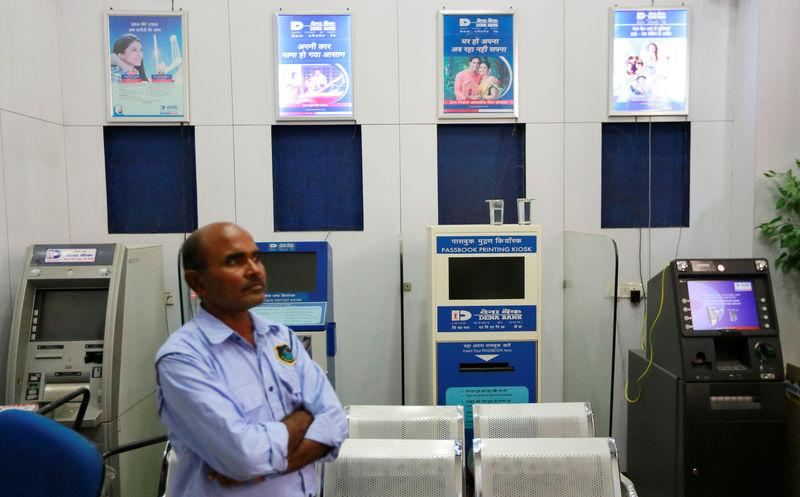 A private security guard stands by an ATM of Dena Bank in New Delhi