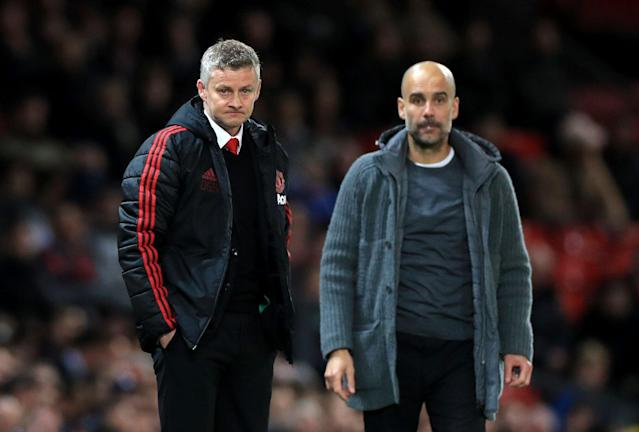 Manchester United manager Ole Gunnar Solskjaer (L) and Manchester City manager Pep Guardiola look on during Wednesday's matchup. (Getty Images)