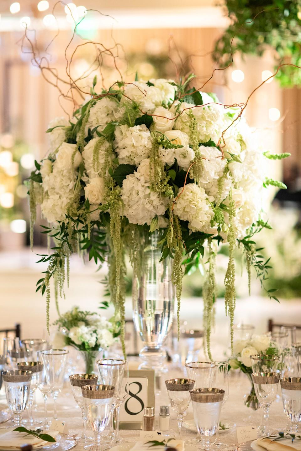 Trumpet vases with all white hydrangeas, lisianthus, roses, orchids, double blooming peonies, and more with amaranthus trailing down.