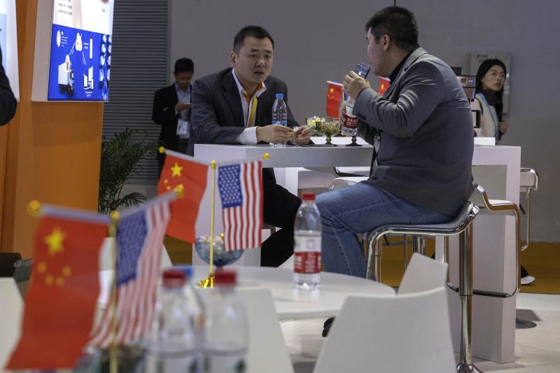 In this photo taken Wednesday, Nov. 6, 2019, visitors chat near American and Chinese flags displayed at a booth for an American company promoting environmental sensors during the China International Import Expo in Shanghai. Washington and Beijing have agreed to cancel tariff hikes as their trade negotiations progress, a Chinese Commerce Ministry spokesman said Thursday, Nov. 7, 2019. (AP Photo/Ng Han Guan)