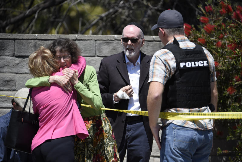 FILE - In this Saturday, April 27, 2019, file photo, two people hug as another talks to a San Diego County Sheriff's deputy outside of the Chabad of Poway synagogue, in Poway, Calif., after a man opened fire inside as worshippers celebrated the last day of a major Jewish holiday. A Jewish civil rights group says anti-Semitic attacks in the U.S. remained near a record-high level in 2018, partially fueled by a sharp increase in physical assaults. (AP Photo/Denis Poroy, File)