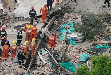 Firefighters work at the site where a building collapsed, in Shanghai, China May 16, 2019. REUTERS/Aly Song