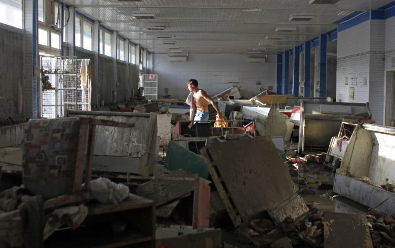 A man removes rubbish from a shop in Krimsk, about 1,200 kilometers (750 miles) south of Moscow, Sunday, July 8, 2012. Intense flooding in the Black Sea region of southern Russia killed at least 150 people after torrential rains dropped nearly a foot of water, forcing many to scramble out of their beds for refuge in trees and on roofs, officials said Saturday. (AP Photo/Sergey Ponomarev)