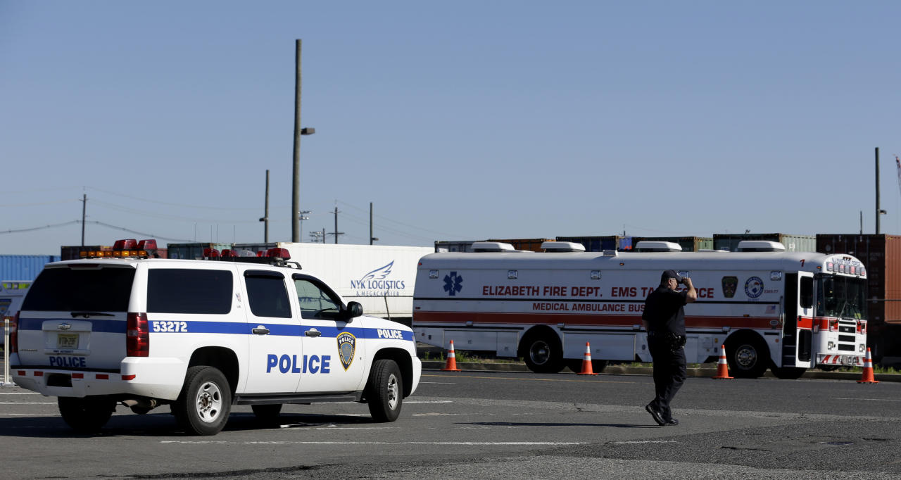 A police official stands near the entrance to a terminal at Port Newark, Wednesday, June 27, 2012, in Newark, N.J. The Coast Guard suspects there are stowaways in a container that was loaded on a ship. Coast Guard spokesman Charles Rowe says a boarding party heard sounds consistent with people coming from the container. The container was loaded aboard The Villa D'Aquarius in India. The manifest says the container was carrying machine parts to be unloaded in Norfolk, Va. (AP Photo/Julio Cortez)