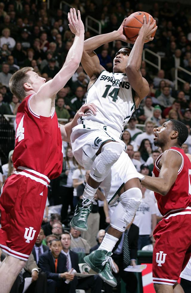 Michigan State's Gary Harris (14) puts up a shot and draws a foul against Indiana's Jeff Howard, left, and Evan Gordon during the second half of an NCAA college basketball game, Tuesday, Jan. 21, 2014, in East Lansing, Mich. Harris led Michigan State with 24 points in a 71-66 win. (AP Photo/Al Goldis)