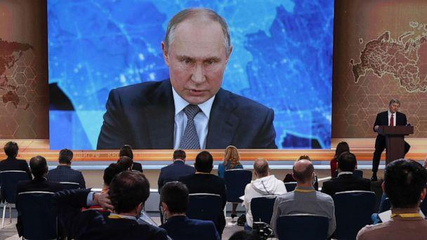 PHOTO: Journalists look at a screen showing Russian President Vladimir Putin speaking during his annual press conference via a video link from the Novo-Ogaryovo state residence, at the World Trade Center in Moscow, Dec. 17, 2020. (Maxim Shipenkov/EPA via Shutterstock)
