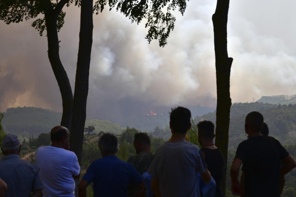 Look residents watch the wildfire near Olympia town, western Greece, Thursday, Aug. 5, 2021. Wildfires rekindled outside Athens and forced more evacuations around southern Greece Thursday as weather conditions worsened and firefighters in a round-the-clock battle stopped the flames just outside the birthplace of the ancient Olympics. (Giannis Spyrounis/ilialive.gr via AP)