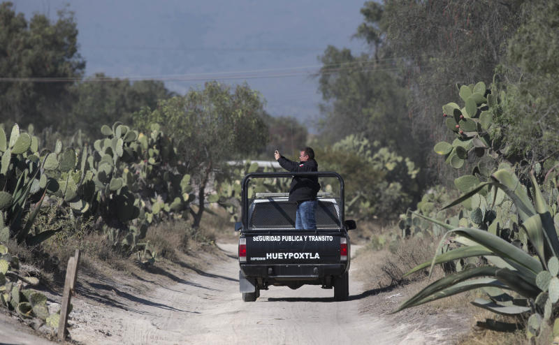 A police documents the surrounding area of the home where authorities found stolen obsolete radiation therapy equipment carried there by a family who found it nearby in the village of Hueypoxtla, Mexico, Friday, Dec. 6, 2013. The truck that was hauling the equipment was found abandoned Wednesday about 40 kilometers (24 miles) from where it was stolen, and the container for the radioactive material was found opened. Authorities continued to work on Friday at the site where the material was found to extract it safely. (AP Photo/Eduardo Verdugo)