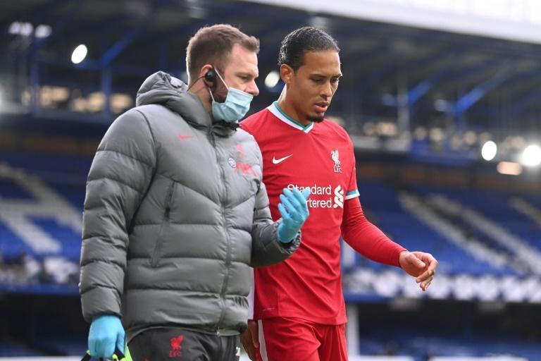 Liverpool defender Virgil van Dijk leaves the pitch with an injury during the Premier League against Everton