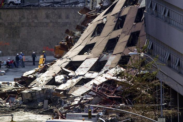 """Why did WTC building 7 collapse when it was not hit by a jet?<br><br>The National Institute of Standards and Technology believe that a combination of fire and severe structural damage caused a """"progressive collapse"""" of the building. <br><br>Photo: Several workers congregate near the collapsed facade of World Trade Center Building 7 in New York Monday, Sept. 17, 2001. (AP Photo/Alan Diaz)"""