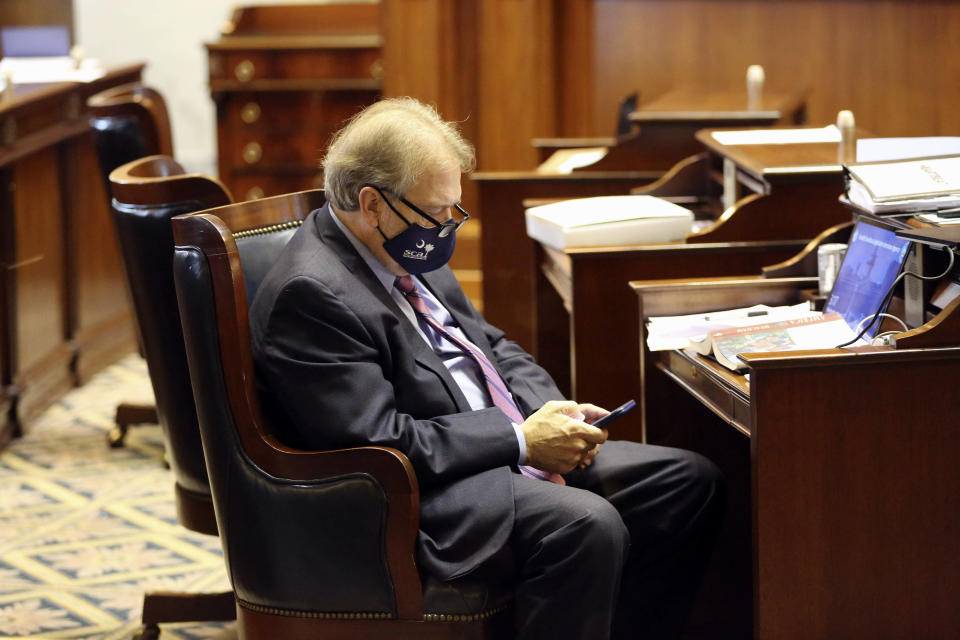 State Senate Minority Leader Brad Hutto, D-Orangeburg, checks his phone during a debate over a bill that would ban almost all abortions in the state on Wednesday, Jan. 27, 2021, in Columbia, S.C. The Senate passed the bill on an initial vote. (AP Photo/Jeffrey Collins)
