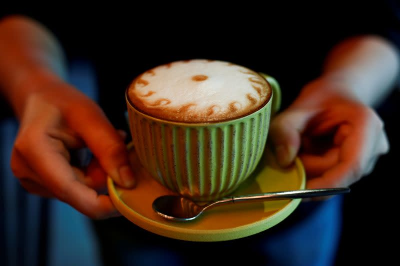 FILE PHOTO: A barista holds a cappuccino coffee at the La Tercera cafe in Beijing