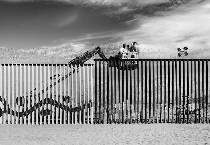 Workers line the top of the border wall with coils of barbed wire in Tijuana, Mexico.