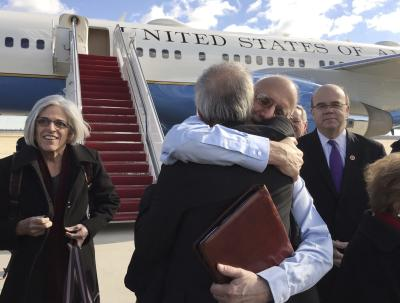 CLICK IMAGE for slideshow: Alan Gross embraces Tim Rieser (C, back to camera), a member of Senator Patrick Leahy's office, on the tarmac as he disembarks from a U.S. government plane with wife Judy (L) at Joint Base Andrews in Maryland outside Washington December 17, 2014 in this photo courtesy of Jill Zuckman. The United States plans to restore diplomatic relations with Cuba more than 50 years after they were severed, a major policy shift after decades of hostile ties with the communist-ruled island, President Barack Obama said on Wednesday. Obama discussed the changes with Cuban President Raul Castro on Tuesday in a telephone call that lasted nearly an hour. Castro spoke in Cuba as Obama made his announcement on a policy shift made possible by the release of American Alan Gross, 65, who had been imprisoned in Cuba for five years. REUTERS/Jill Zuckman/Gross Family spokesperson/Handout via Reuters (UNITED STATES - Tags: POLITICS) ATTENTION EDITORS - THIS PICTURE WAS PROVIDED BY A THIRD PARTY. REUTERS IS UNABLE TO INDEPENDENTLY VERIFY THE AUTHENTICITY, CONTENT, LOCATION OR DATE OF THIS IMAGE. FOR EDITORIAL USE ONLY. NOT FOR SALE FOR MARKETING OR ADVERTISING CAMPAIGNS. NO SALES. NO ARCHIVES. THIS PICTURE WAS PROCESSED BY REUTERS TO ENHANCE QUALITY. AN UNPROCESSED VERSION WILL BE PROVIDED SEPARATELY