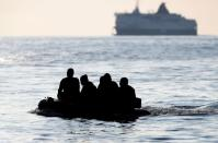 FILE PHOTO: People who say they are from Darfur, Sudan cross the English Channel in an inflatable boat near Dover