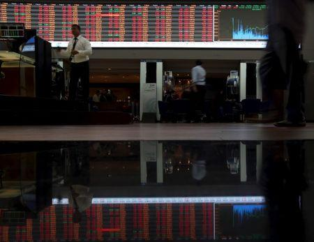 People walk past the stock quotation board on the floor of Brazil's BM&F Bovespa Stock Market in Sao Paulo August 24, 2015. REUTERS/Paulo Whitaker