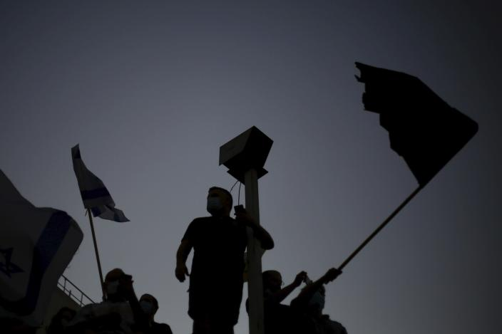 Protesters wave flags outside of the Prime Minister's residence in Jerusalem, Tuesday, July 14, 2020. Thousands of Israelis on Tuesday demonstrated outside the official residence of Prime Minister Benjamin Netanyahu, calling on the embattled Israeli leader to resign as he faces a trial on corruption charges and grapples with a deepening coronavirus crisis. (AP Photo/Ariel Schalit)