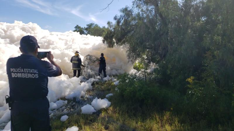 Crews look through a large wall of soap suds at Valsequillo reservoir in Puebla, Mexico for a missing man who fell in. He was later found dead.