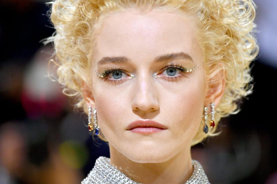 """<p>Why do a black winged liner when you can do a silver gem-encrusted winged liner instead? It seems that Julia Garner and <a href=""""https://www.instagram.com/patmcgrathreal/"""" class=""""link rapid-noclick-resp"""" rel=""""nofollow noopener"""" target=""""_blank"""" data-ylk=""""slk:makeup artist Pat McGrath"""">makeup artist Pat McGrath</a> thought just that. On the red carpet, Garner wore five tiny individual gems placed from the outer corners of her eyes extending up towards her temples and three smaller gems on the inner corners of her eyes.</p>"""