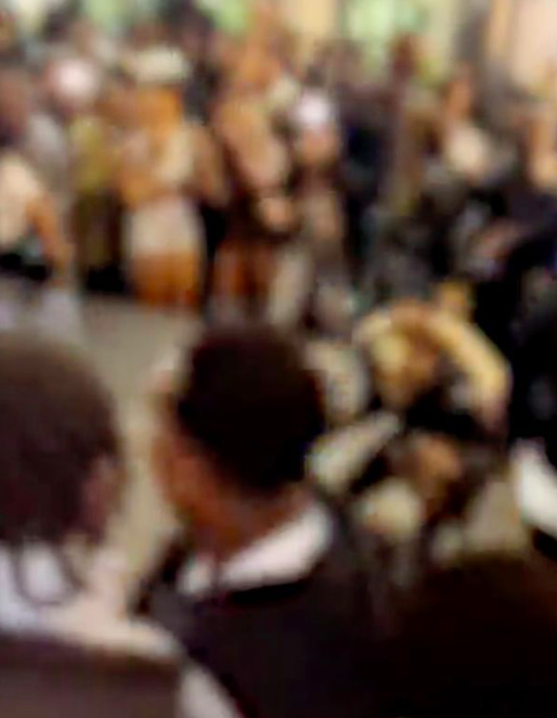 The tightly-packed crowd is shown holding up mobile phones. (Reach)