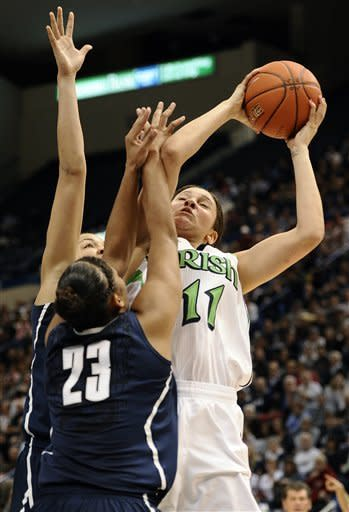 Notre Dame's Natalie Achonwa (11) goes up to the basket while guarded by Connecticut's Kaleena Mosqueda-Lewis (23) and Connecticut's Kiah Stokes, back, first half of an NCAA college basketball game in the final of the Big East Conference women's tournament in Hartford, Conn., Tuesday, March 12, 2013. (AP Photo/Jessica Hill)