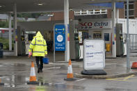 A closed petrol station in Manchester, England, Tuesday, Sept. 28, 2021. Long lines of vehicles have formed at many gas stations around Britain since Friday, causing spillover traffic jams on busy roads. (AP Photo/Jon Super)